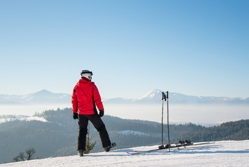 Rearview shot of a skier resting after the ride standing on top of the ski slope looking around enjoying breathtaking view of snowy mountains on a sunny winter day seasonal recreational extreme active