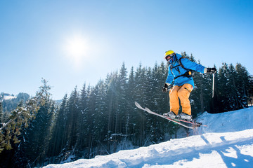 Professional skier jumping in the air while skiing in the mountains blue sky on the background copyspace sunlight extreme freeride adrenaline sportsman activity enjoyment at the winter ski resort