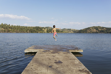 Boy jumping in lake.