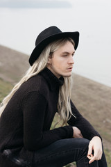 Portrait of a male model with long hair and black hat sitting near river