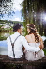 Young wedding couple sitting on a bench