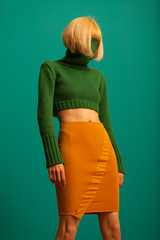 young woman with yellow skirt and green sweater standing