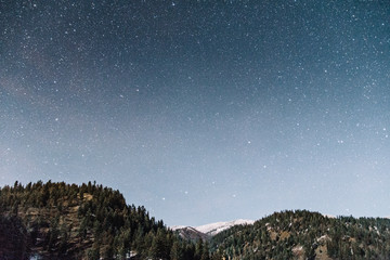 Starry sky over mountains with fresh snow.