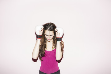 Young woman with kick boxing gloves looking down