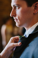 Best man in wedding having corsage pinned to lapel
