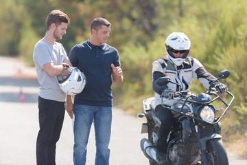 driver instructor controls motorbike pilot
