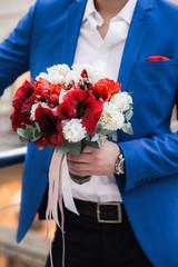 Groom wearing blue jacket holding red wedding bouquet