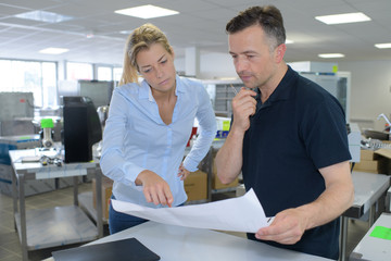 smiling young business man and woman in office