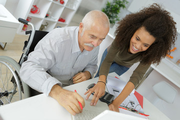 young woman helping senior disabled man to fill paper documents