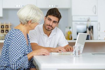 grandson showing senior woman online computer use