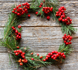Christmas wreath of pine branches and red Rowan on wooden background. Copy space.