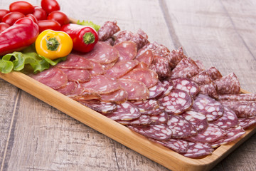 Set of meat delicatessen, tomatoes and peppers on a wooden table.