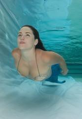 Woman wearing shell bikini and mermaid tale.