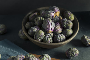 Wooden bowl of green and purple Brussel sprouts