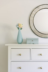 Flower vase and jewelry box on cabinet