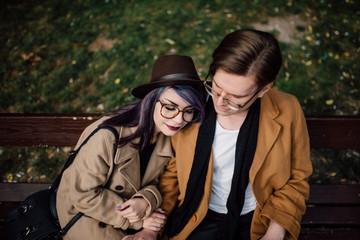 Young stylish couple hugging on the bench