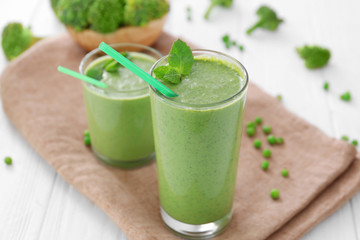 Healthy smoothie with kale in glasses on table