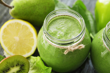 Healthy smoothie with kale in glass jar on table