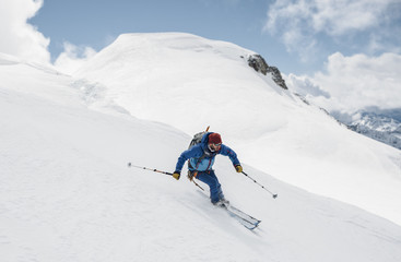 young male freerider skiing down a powder hill from a glacier in the Alpine mountain