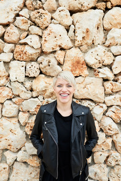 Smiling blondie on stone wall background.