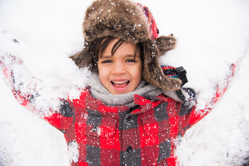 smiling child making a snow angel