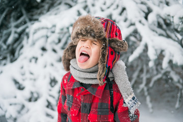 child sticks tongue out to catch falling snowflakes