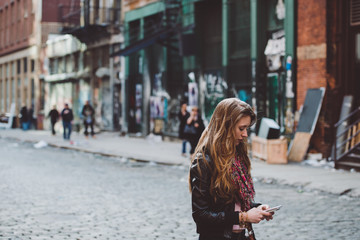 Young woman on her phone in the city