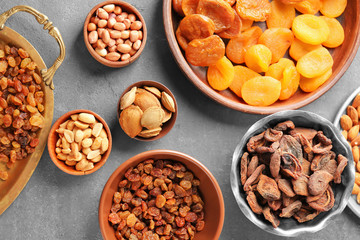 Dried apricots, raisins and nuts in different dishes on table
