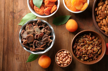 Dried apricots, raisins and nuts in different dishes on wooden table