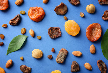 Dried apricots, raisins and nuts on color background