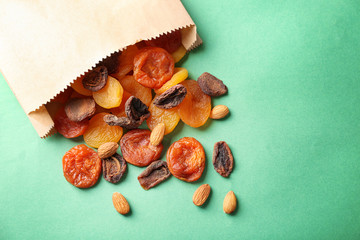 Paper bag with dried apricots and nuts on color background