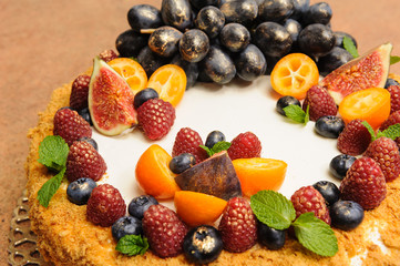 Beautiful large honey cake decorated with fruits and berries on top with pears and sea buckthorn  gold kandurin, grapes, figs, kumquat, on a wooden table.