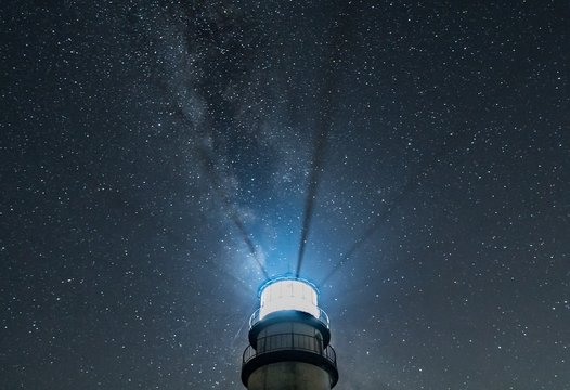 Lighthouse beams at night with starry sky and Milky Way