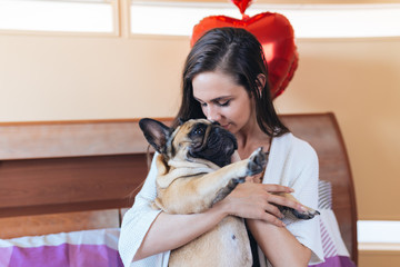 Attractive young woman enjoying on bed with her french bulldog pet.