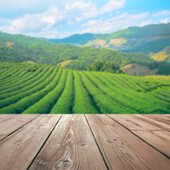 wooden table top with blurred tea plantation background