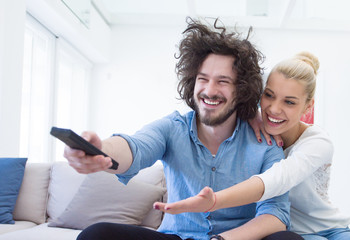Young couple on the sofa watching television