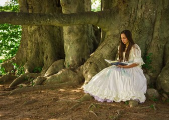 girl reading in white dress by trees