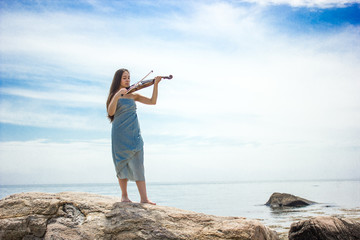 girl in blue playing violin by ocean