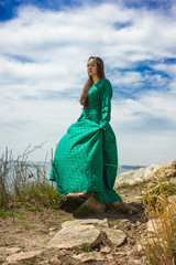 girl in green medieval dress on cliff