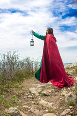 girl by ocean with lantern and red cape