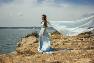 Girl in blue dress on a cliff 1