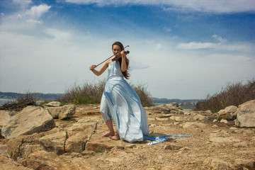 Girl playing violin at the beach in blue 9
