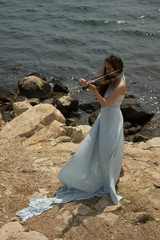 Girl playing violin at the beach in blue 5