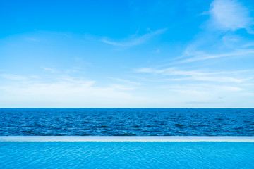 Infinity swimming pool with sea and ocean view on blue sky