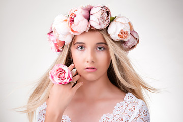 Beauty portrait. Beautiful blonde girl with wreath of flowers. Looking at camera.