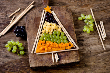 Christmas cheese and grape tree on a wooden board