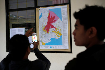 A man takes a picture of a map of the danger zones around Mount Agung, a day after the volcano's alert status was raised to the highest level, at a government monitoring station and observatory in Rendang, on the resort island of Bali