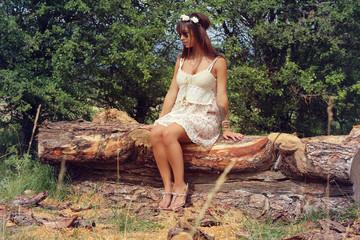Beautiful fashion woman sitting on a tree