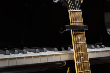 acoustic guitar with capo against grand piano keys - closeup musical instruments concept for musical composition and creativity