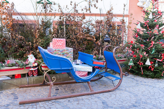Blue vintage sleigh with presents in the winter with a decorated christmas tree